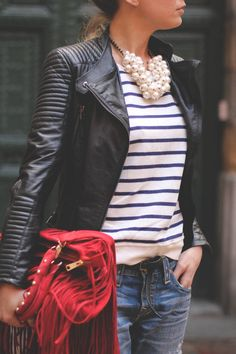 Black jacket, white and black stripe shirt, pearly statement necklace, jeans, red bag