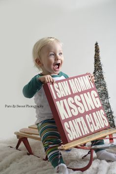 a child or children holding this sign with the mommy and daddy in the background kissing with dad wearing a santa suit. Baby Christmas Photos, Christmas Mini Sessions, Christmas Minis, Xmas Pics, Christmas Photography Kids, Holiday Photography, Children Photography, Holiday Pictures, Picture Ideas