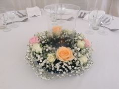 A crown of flowers encircle the storm glass vase with candle. Ellerymay La Fleuriste