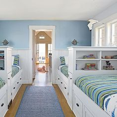 A long narrow space on the second floor of this Kennebunkport, Maine, cottage became the perfect place for a row of bunks. Built-in shelves double as headboards, and drawers underneath are perfect for stowing clothes and toys.