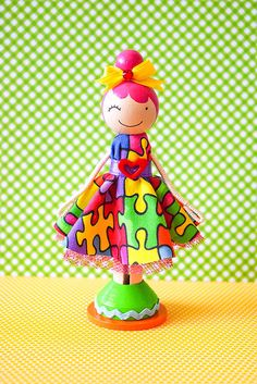 "Brooke Autism Awareness Miniature Wooden Clothespin Doll-""Brooke"", a super cute wooden clothespin doll stands just over four inches tall, and is uniquely hand painted in vibrant colors and wears a real cotton fabric dress in a puzzle piece print, with pink tulle underskirting"