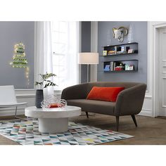 """I'm not wild about the rug but I love the combination of the deep gray wall, bent metal wall shelves, gray rue bayoux sofa with  36""""x16"""" orange-red pillow."""