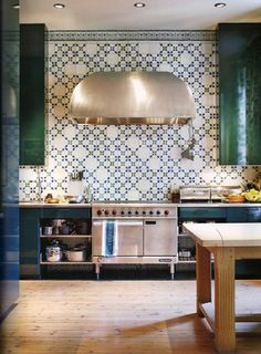 patterned tile / silver range hood / dark green cabinets / tall cabinets