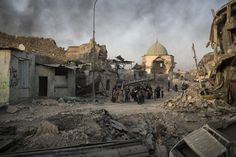 Fleeing civilians walk past the heavily damaged al-Nuri mosque as smoke rises in the background in the Old City of Mosul, Iraq. (Felipe Dana / AP) http://pow.photos/2017/international-pow-4-10-july/