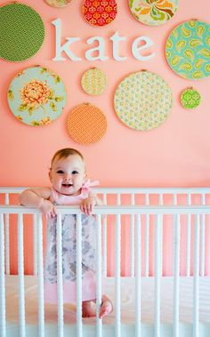 Name on wall . DIY Nursery Wall - pink and green nursery inspiration. Fabric Disc panels are a good idea and should be easy to make.