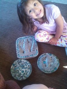 """Stepping stones with foot prints & cheap (Dollar Tree) """"rocks"""" in them. Very easy to make! All we used was a few disposable pans (pie pans & lasagna pans), some cheap colorful rocks, and some quick set cement. VERY easy & Their mom loved it for a great Mother's Day gift! :) The kids were able to put the stones all over & their foot prints in them too. They loved this project"""