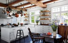 In the kitchen of the Martha's Vineyard retreat of Lynn Forester de Rothschild and her husband, Sir Evelyn, a Ralph Lauren Paint white was used on the Rivkin/Weisman–designed cabinetry, and the antique granite flooring is from Exquisite Surfaces. The pot rack is from Ann-Morris, the reclaimed-oak open shelves feature brackets by Rocky Mountain Hardware, and the backsplash tile and farmhouse sink are by Waterworks. Architect Hugh Weisman and decorator Mark Cunningham renovated the home.