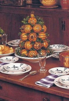 Williamsburg Pomander Centerpiece - Consists of cone-shaped wooden form 10 inches high, 5 inches wide at the base, and 2 1/2 inches wide at the top (available through Colonial Williamsburg), oranges, whole cloved, and sprigs boxwood for filler