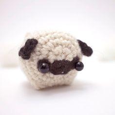 Aquí es un perro pequeño pug. Pug te mantendrá compañía en tu estantería o escritorio y es lo suficientemente pequeño como para caber en su bolsillo - perfecto para los amantes del pug. Tuyo puede hacerse también en un llavero o colgante de adorno. Esta pieza de amigurumi está a sólo 5 cm/2 de largo y 4 cm/1.6 amplia. Es de punto con mezcla de lana y se llena con relleno de poliéster reciclado. Pug es concebido como un animal de peluche coleccionable y no es adecuado para los niños. En...