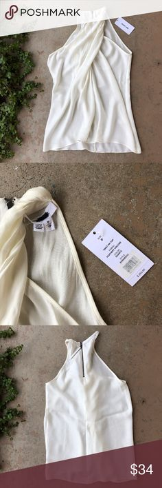 NWT Helmut Lang Cream Twist Halter Tank Helmut Lang twist top in a pretty cream color. Size P (which fits an XS). While this is new with its $255 retail tag attached, note that there are a couple places at the seam with minor damage. See pictures for details. Helmut Lang Tops Tank Tops