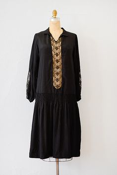 1920's black silk crepe dress features drop waist with smocked gathers on the sides. V-neck has small collar and bodice features sheer lace panel on front. Slightly puffed sleeves have banded hems and is accented with a small grosgrain bow. Lace on sleeves is tonal black and brown.