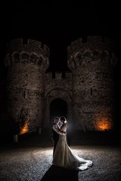 Cooling castle wedding photographer night shot with castle ruins illuminated silhouette
