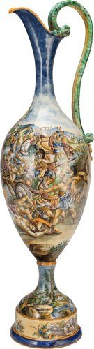 A MONUMENTAL ITALIAN MAJOLICA EWER, circa 1890 51 inches high (129.5 cm) The ewer with a bifurcated serpent-form handle, painted continuous battle scene to the body, raised on a circular foot with putti and shell decoration.