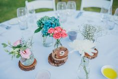 Vineyard wedding- Tables set under the stars. Wood slabs and mixed jars of blooms.