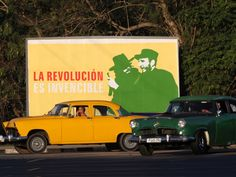 Cuba - Old cars drive near a banner with images of rebel revolutionary Camilo Cienfuegos, left, and ex-president Fidel Castro in Havana.