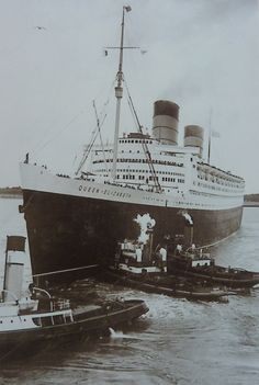 The Queen Elizabeth being assisted by tugboats. Source.