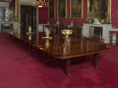 Located 2015 in the Music Room of Buckingham Palace, London, UK. Mahogany Dining Table made in UK. Extending Dining Table with 9 removable leaves on Legs carved with Lotus Leaves, on castors.