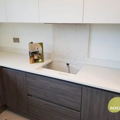 A contemporary wood grain kitchen featuring the Attica White Carrera Quartz. It goes perfectly together with the white cabinets above. #WhiteQuartz #AtticaWhiteCarrera #MarbleQuartz #QuartzWorktops