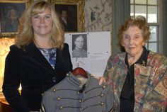 In this photo taken Wednesday Nov. 28 2012 in Onacock, Va., Donna Gugger, left, and Teresa deGavre, pose with the West Point uniform jacket Gugger found on a beach in New Jersey after Superstorm Sandy. The jacket belonged to deGavre's late husband Chester B. deGavre, a U.S. Army Brig. General. Gugger returned the jacket to deGavre's widow, who now lives in Virginia. (AP Photo/Eastern Shore News, Malissa Watterson)