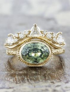 Reveniss, hand engraved green sapphire oval solitaire engagement ring, in a bezel setting. by Ken & Dana Design.