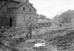 A Sherman tank crewman finds the mud heavy going in the Hürtgen