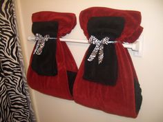 Hanging bathroom towels decoratively. I absolutely love this:) plus the Red & Zebra!!!