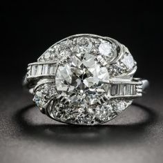A bright-white and shining European-cut diamond, weighing 1.84 carats, sparkles loud and proud in this singular and spectacular original Art Deco dazzler, hand fabricated in platinum, circa 1920s-30s. The scintillating stone is embraced in an artfully stylized yin/yang motif mounting studded with glittering round and baguette diamonds, together weighing .90 carat, for an impressively stunning effect. Currently ring size 6.