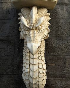 Dragon Corbel ~ Elegant and finely detailed Dragon Corbel. Perfect as an unusual base for a candle or lamp, or as a mock support for a beam, mantelpiece, or fireplace. Cast by hand in frost proof casting stone the Dragon Corbel is suitable for indoors or year round outdoor use. He is 15cm wide, 31cm high, and weighs approximately 4kg.