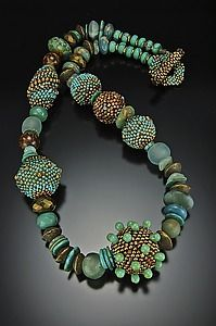 "Turquoise and Gold Patina Necklace""  Created byJulie Powell     Limited Edition     Glass seed beads woven around a hollow wooden bead, with a needle and filament, bead by bead. Czech and Japanese glass, Fire polished glass, Recycled glass from Africa, brass, Turquoise, Afghan Jade and Tigers Eye."