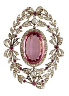 Pink topaz and diamond brooch, circa 1910. Edwardian diamond-set open work oval brooch, set with an oval-cut pink topaz to centre weighing approximately 9.00cts within a diamond-set bow and garland surmount. Millegrain setting, mounted in platinum.