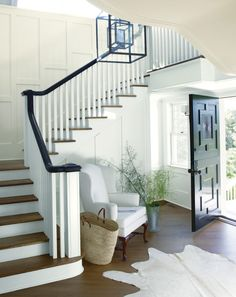 A light-filled entryway with open front door features a wing chair in the curve of a staircase.