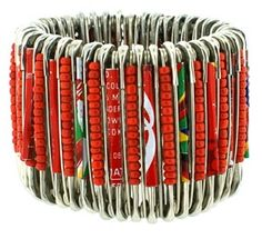 Alternating on a safety-pin base with red seed beads are South African beads fashioned from recycled Coca-Cola cans.