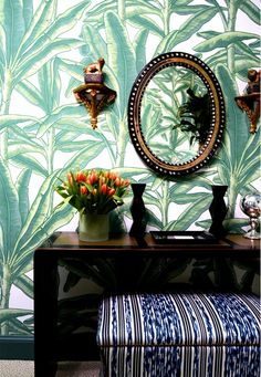 Palm print wallpaper, patterned ottoman, bright flowers and antique sconces and mirror.