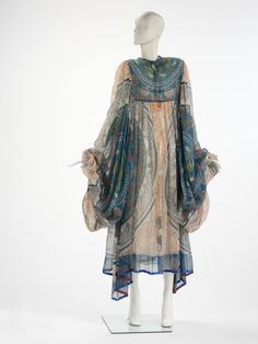 """Evening Dress, Zandra Rhodes (1940-), UK: 1969, printed silk chiffon. """"This kaftan-style dress comes from Zandra Rhodes' first independent collection, called 'Knitted Circle'. The collection consisted of garments made with her distinctive, hand- printed silks designed with motifs taken from knitting and embroidery stitches. Zandra Rhodes later wrote 'I made swirling, dramatic shapes with no concessions to the saleable, the acceptable or the ordinary. The true Rhodes style came into being'."""""""