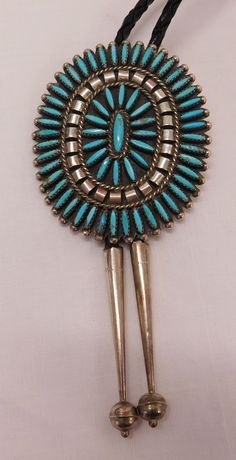 """436: S.S. & Turquoise Needlepoint Bolo Tie, 20th century item. Made of sterling silver, turquoise and leather, the item hangs 19"""" as worn. The bolo portion measures 2.25"""" x 2.75"""" and weighs approx. 38 grams w/drops. Zuni, New Mexico. Signed CJ. Over 60 stones inlaid in this large, eye-catching bolo tie with 2 inch sterling drops. Condition: Very good, see images. Shipping: $15.50 w/insurance and signature."""