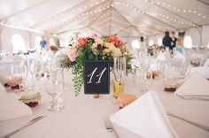 Reception under the wedding tent at Highland Springs Resort.  Chaffin Cade Photography. Light colors. Pink and Peach wedding. Garden Arranement. Chalk board table numbers. Spring wedding table decor