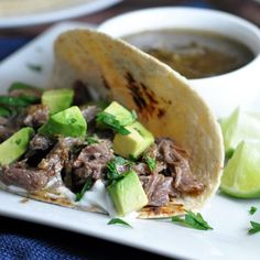 Meat cooks all day in an awesome tomatillo salsa, then shredded, and topped with ripe avocado and tangy lime juice.