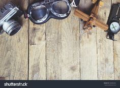 Vintage Retro Travel Background. Retro Camera, Glasses, Balsa Wood Model Airplane And Compass On Wooden Table Background.…