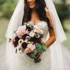 This stunning real Morilee by Madeline Gardner Bride is holding a lush bridal bouquet of blush, Burgundy wine, and white flowers with Navy centers. Wedding Dress style 2623. Photo by Shari and Mike Photography.