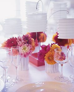 Wedding Centerpieces    Small paper lanterns dangle from the centerpiece of each table. Around them, paper blooms mingle with fresh-cut dahlias