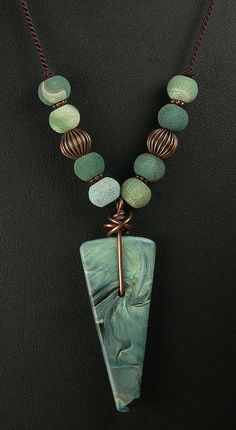 """Polymer Clay Pendant Beaded Necklace by WiredOrchidJewelry on Etsy. The subtle, swirled green and black pattern of this polymer clay pendant is a contrast to the necklace's bold design. The triangle pendant is attached to a strand of fire agate beads and copper beads and spacers with a unique, handmade copper bail which has been treated with a patina. Necklace is 21"""" in lenghth."""