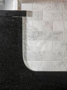 Carrara Marble Subway Backsplash Design with black pearl granite. BM Cloud White painted cabinets, silver hardware, walnut stained oak hardwood flooring.
