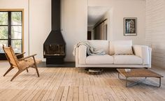 simple country farmhouse vibes | burlap walls and rough hewn floors | black iron wrought fireplace | IKEA Nockeby sofa with a Bemz cover in Eggshell Zaragoza Vintage Velvet | rattan chair