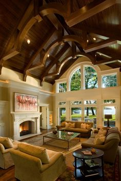 A fabulous living room features a vaulted ceiling of wood, and exposed beams with a center barrel shape that mimics the arched transom window above the French doors.