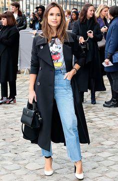 Miroslava Duma usa t-shirt do mickey com calça jeans reta, maxi casaco e scarpin branco