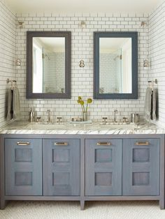 Contemporary bathroom features mini-subway tiled nook filled with blue wash, beveled mirrors over blue wash, double vanity topped with white and grey marble illuminated by mini glass and metal pendants atop mosaic marble floor