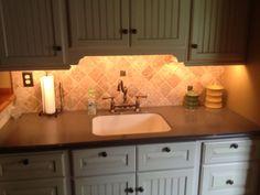 Under cabinet lighting + beaded board cabinets = love