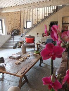Le garde corps en acier de l'escalier donne un esprit industriel au salon et le modernise en contrastant avec la pierre des murs et les poutres apparentes du plafond. Le béton des marches est prolongé grâce au revêtement du sol. En savoir plus sur http://www.cotemaison.fr/espace/7-idees-d-escalier-avec-ou-sans-rampe_17382.html#z8F6UdJOCWfRCvPB.99