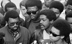 Bobby Seale (right), chairman of the Black Panther Party, is one of three speakers at a sidewalk news conference in Oakland, Calif., on Nov. 21, 1968. The other speakers are Ben Stewart (left), head of the Black Students Organization at San Francisco State, and George Murray (center, dark glasses), suspended teacher at San Francisco State.