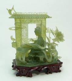 """CHINESE CARVED SERPENTINE JADE GROUP. A nicely carved Chinese translucent green serpentine jade sculpture depicting a meiren playing a zheng. Behind her is wall with moving reticulated windows. Surrounded by foliage and flying birds. Includes fitted wooden base. Circa 19th/20th century. 7 1/4"""" height x 6"""" width (18.4cm x 15.2cm). Jade weight of 528 grams. Via eliteauction.com"""